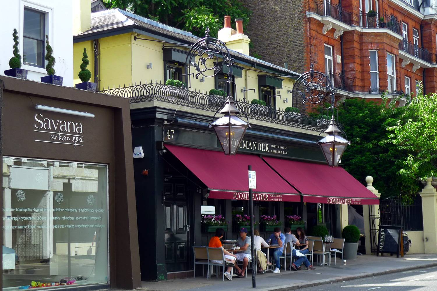 Image of people sitting outdoors in front of a London neighborhood pub.