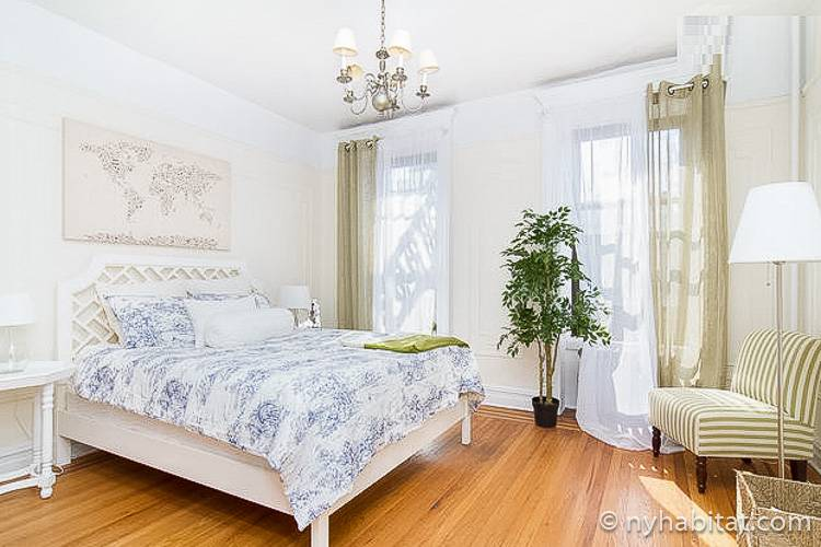 Image of bedroom in NY-16310 with queen-sized bed and potted plant.
