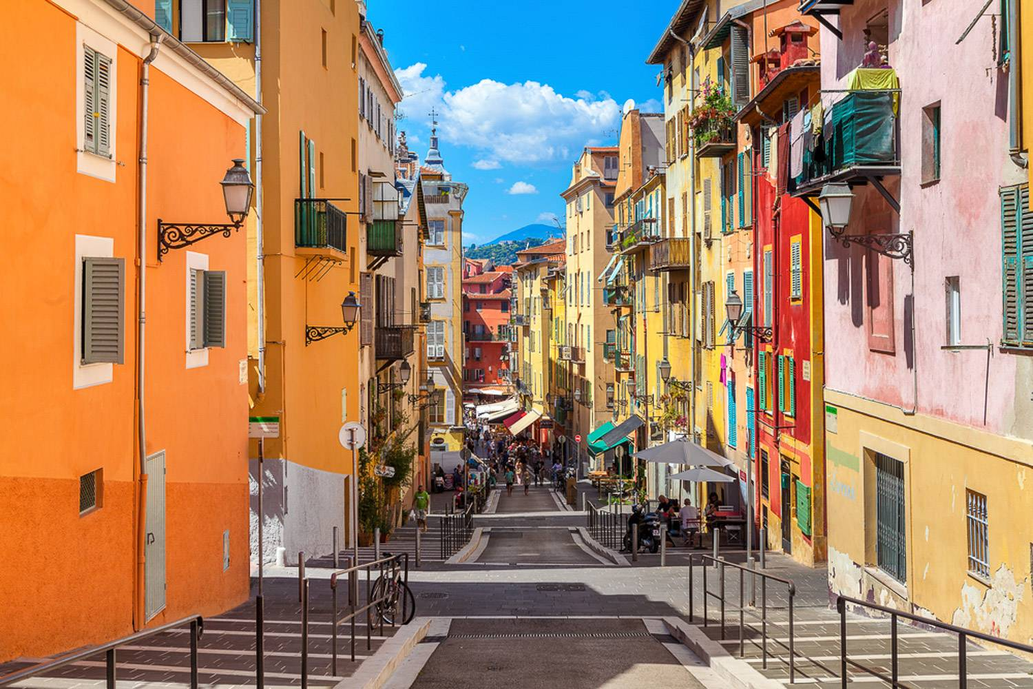 Image of a cobblestone street surrounded by colorful buildings in Old Nice.