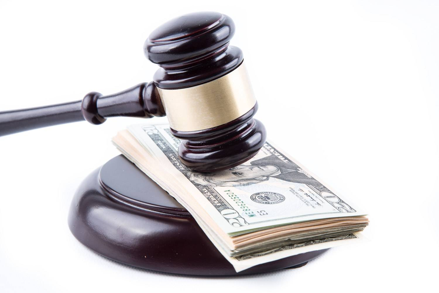 Image of a judge's gavel over a stack of dollar bills.