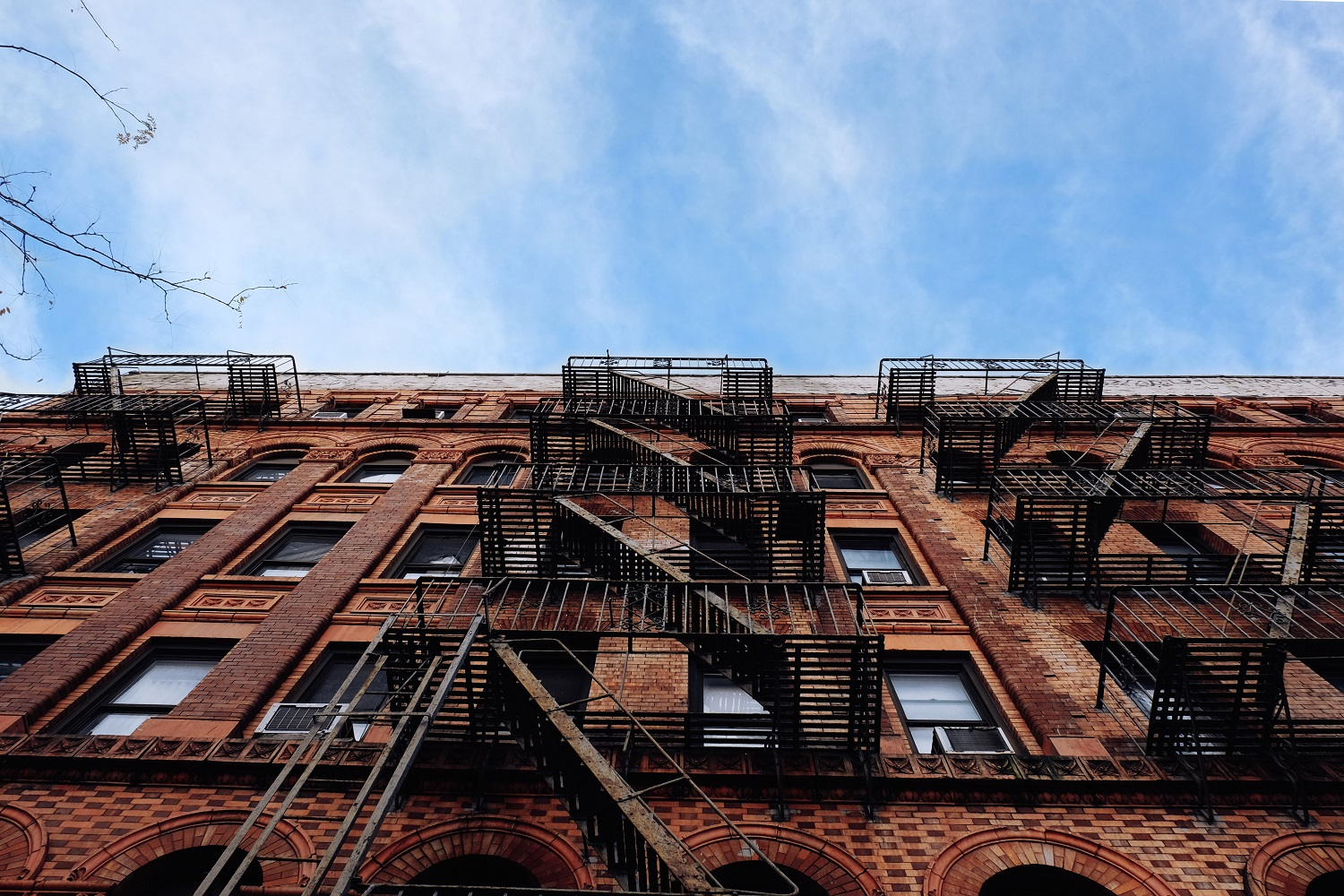 Image of a brick façade of mid-rise apartment buildings with fire escapes in New York City.
