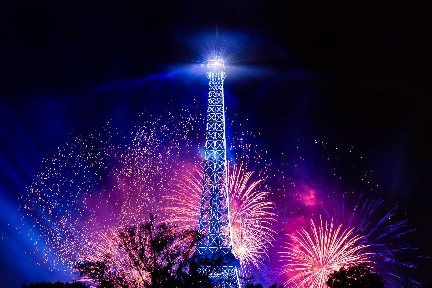 Image of fireworks exploding behind the Eiffel Tower on Bastille Day.