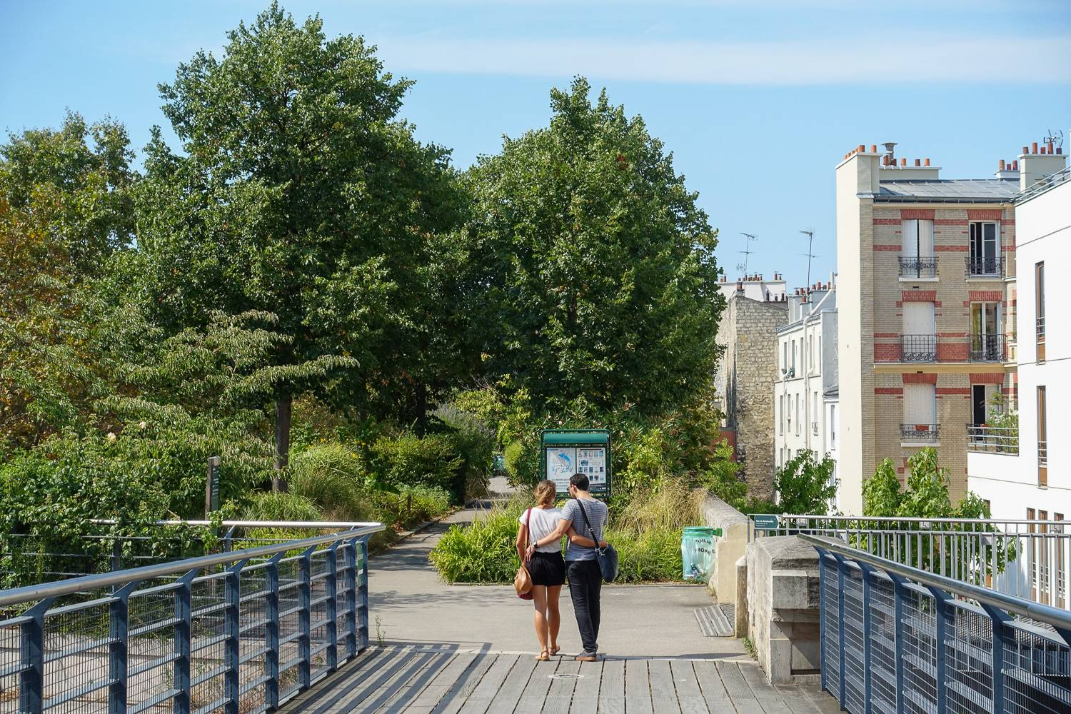 Image of a couple walking on the Coulée vert René-Dumont in summertime.