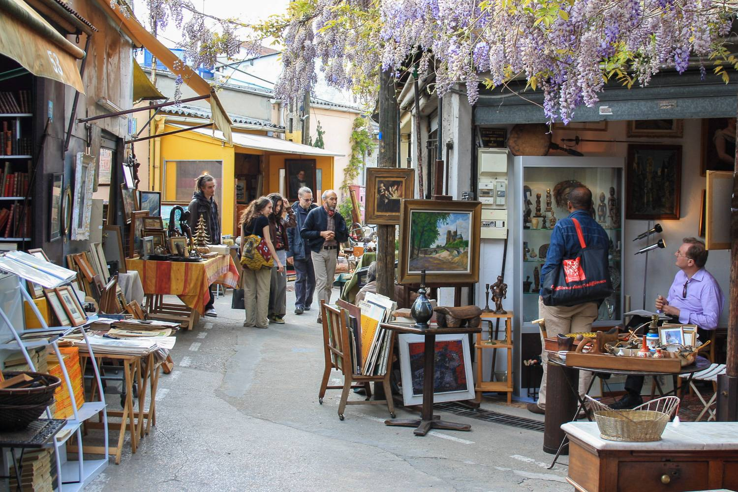 Image of people walking between antiques stalls in the Puces de Saint-Ouen outdoor flea market.
