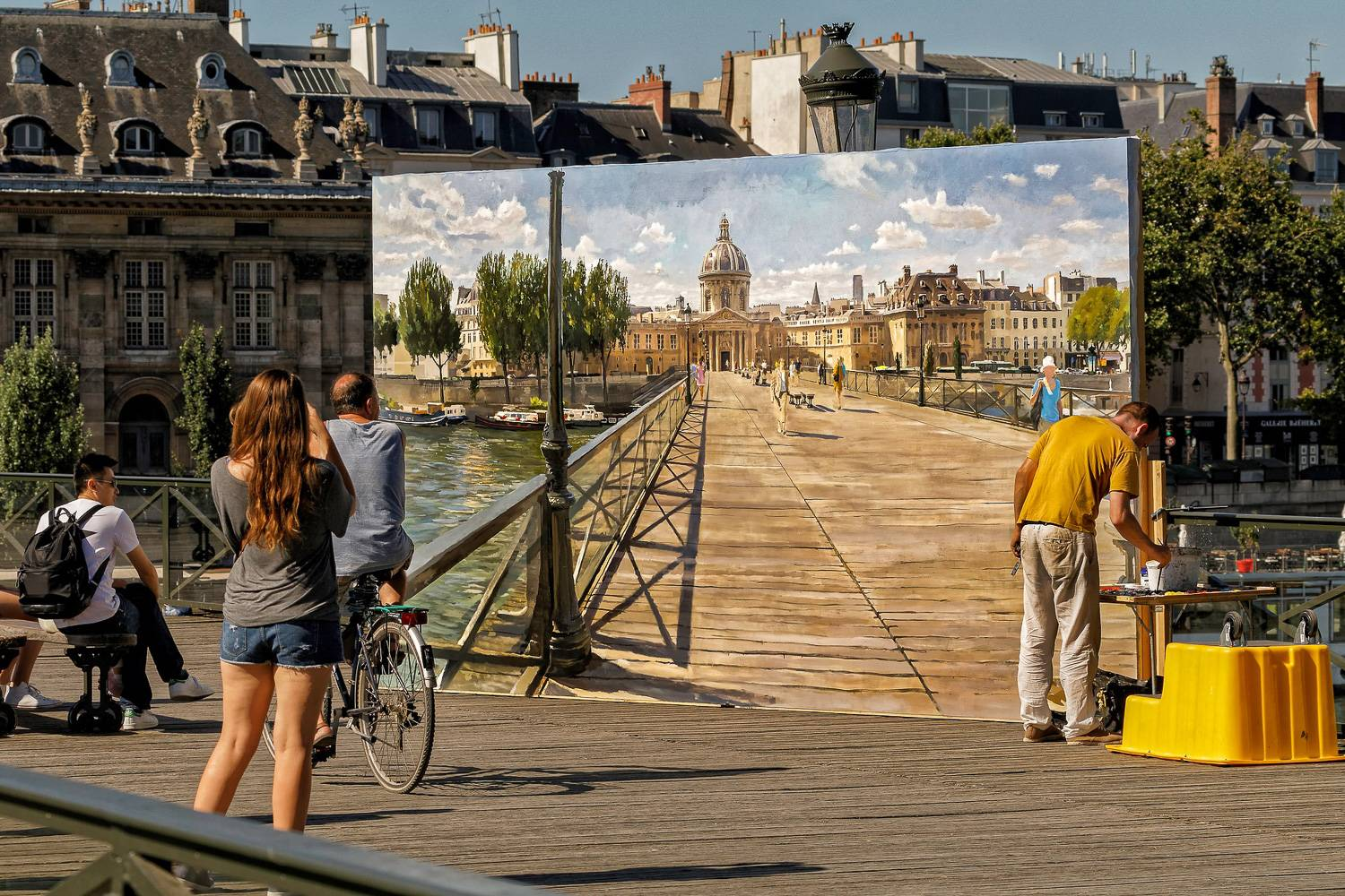 Image of pedestrians and cyclists crossing a bridge over the Seine River while an artist paints the scene.