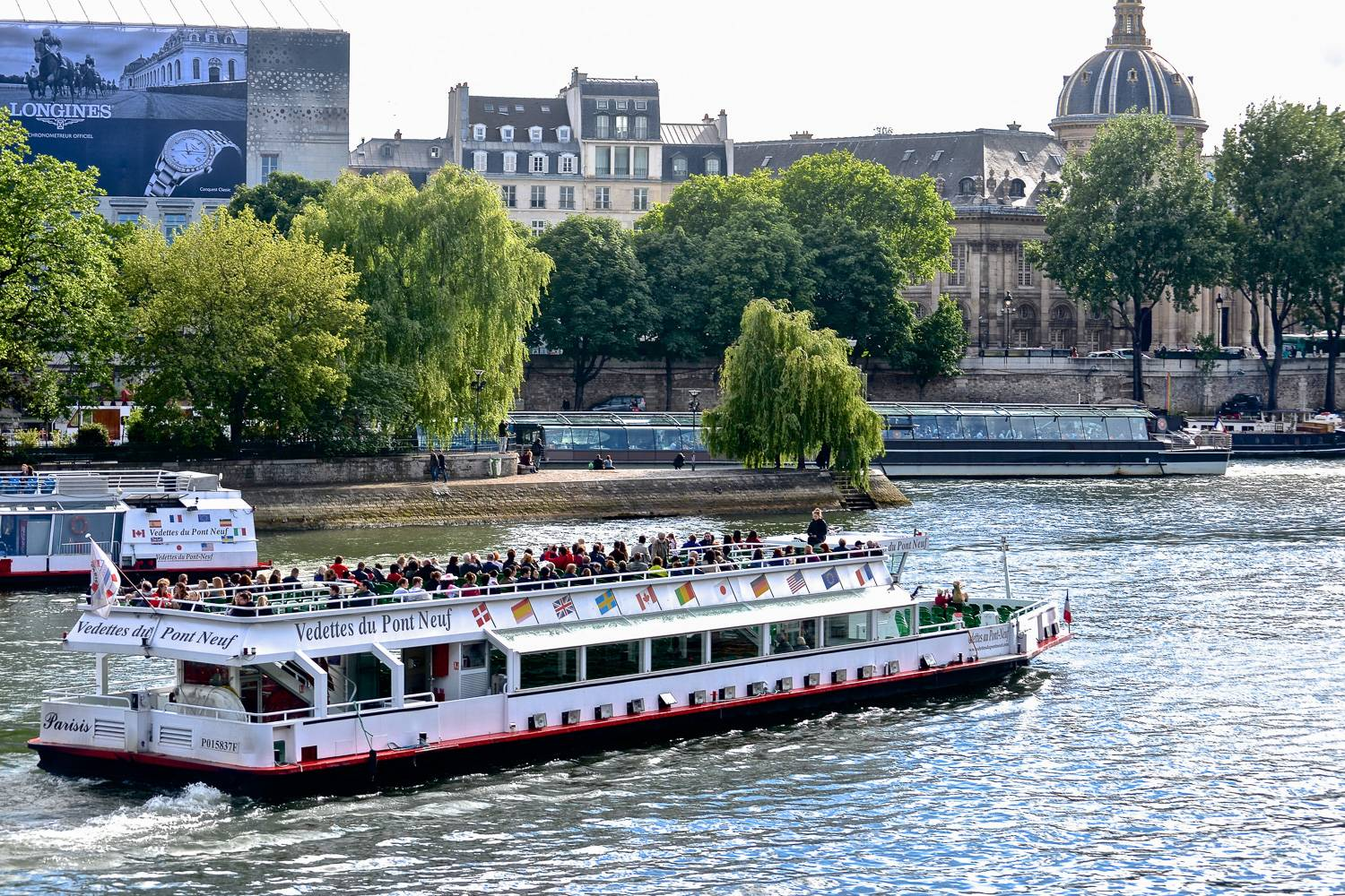 Image of a cruise boat filled with sightseers on the Seine in Paris.