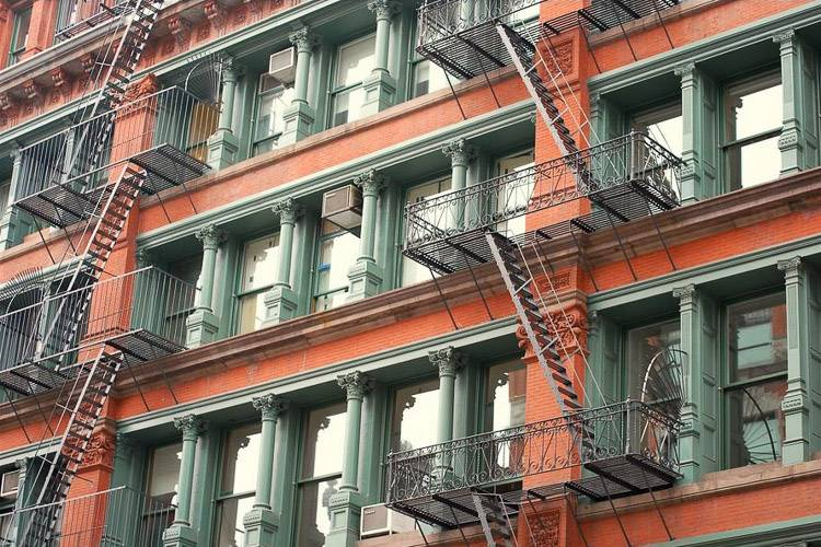 Image of fire escapes on a red brick building in New York City.