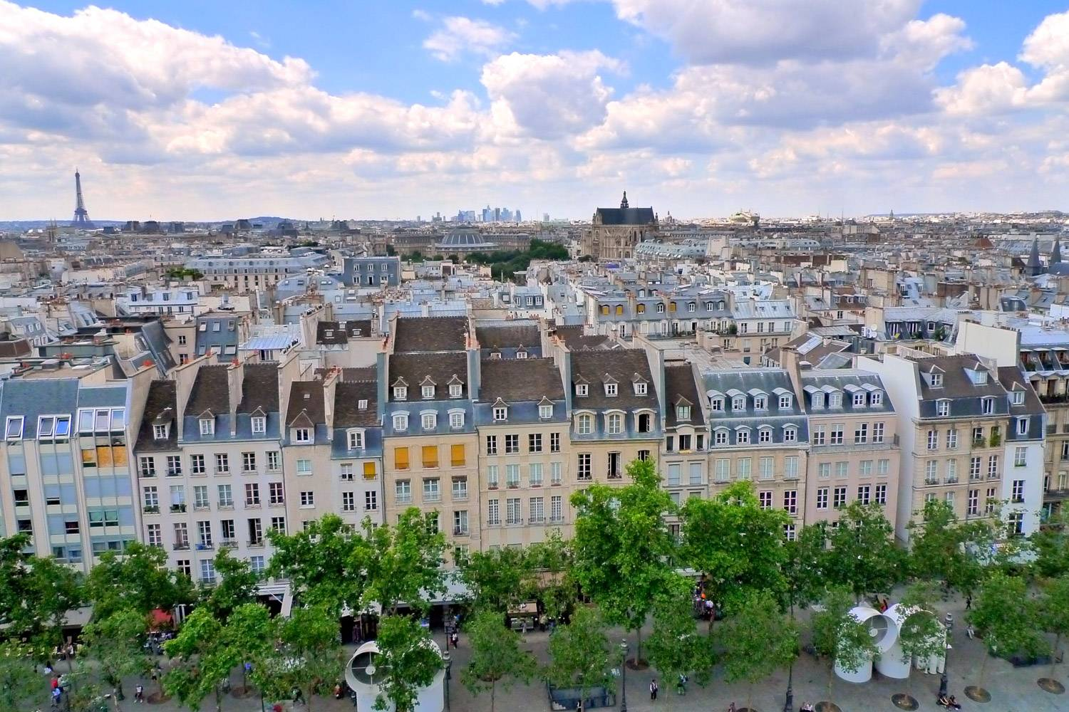 Image of Paris skyline over rooftops on a sunny day.
