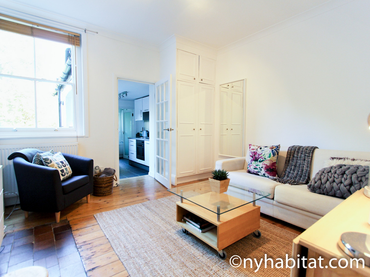 Image of living area in LN-24 with white sofa and armchair.