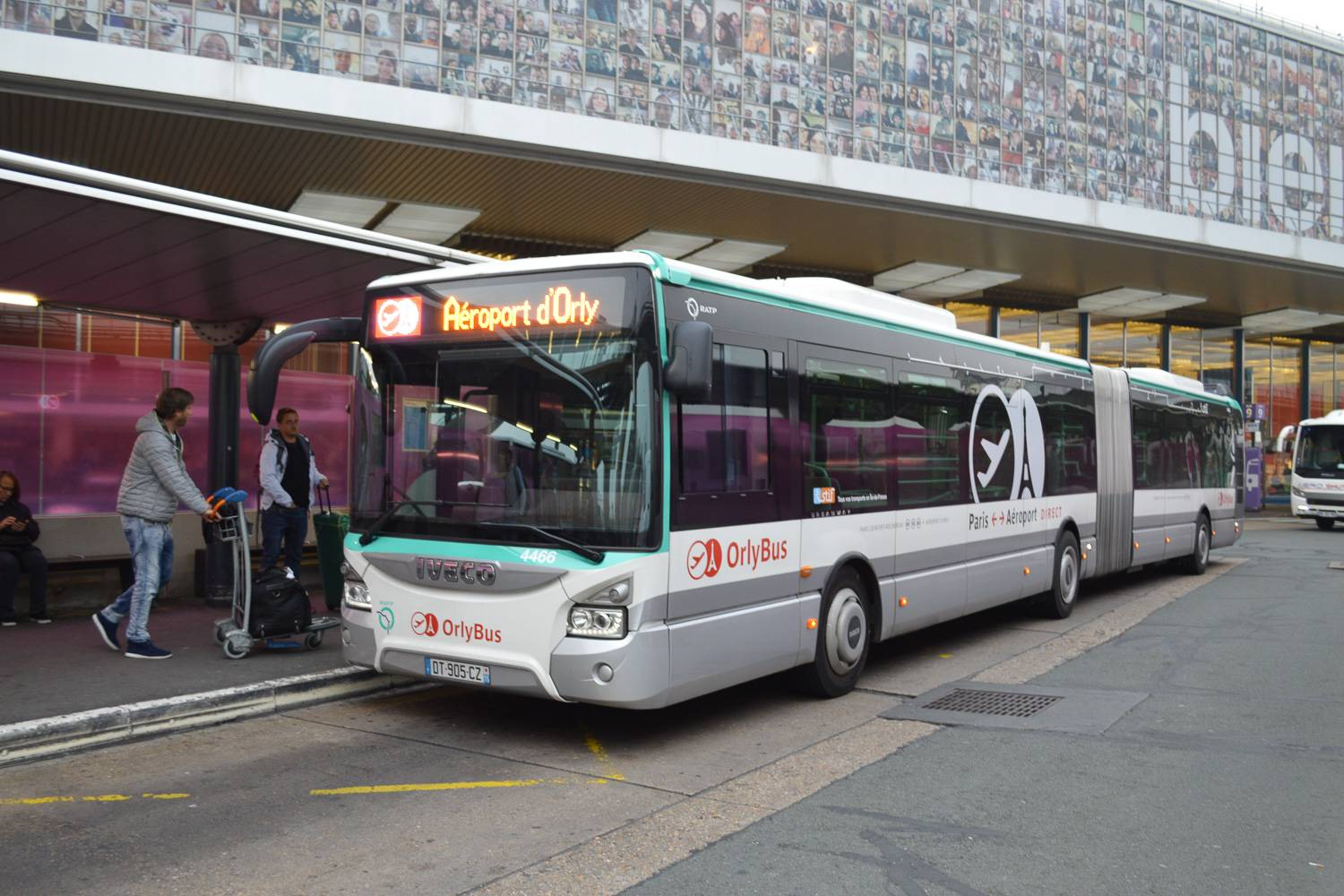 Image of an Orlybus picking up passengers at the curb of Orly Airport.