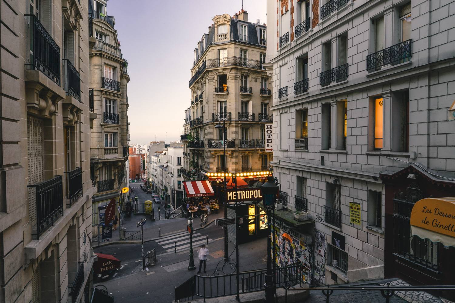 Image of a Paris street from the top of a set of stairs at dusk.
