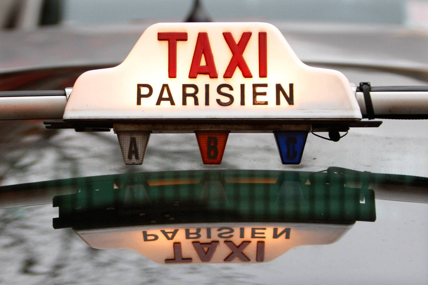 Image of illuminated Taxi Parisien sign on the roof of a Paris taxi.