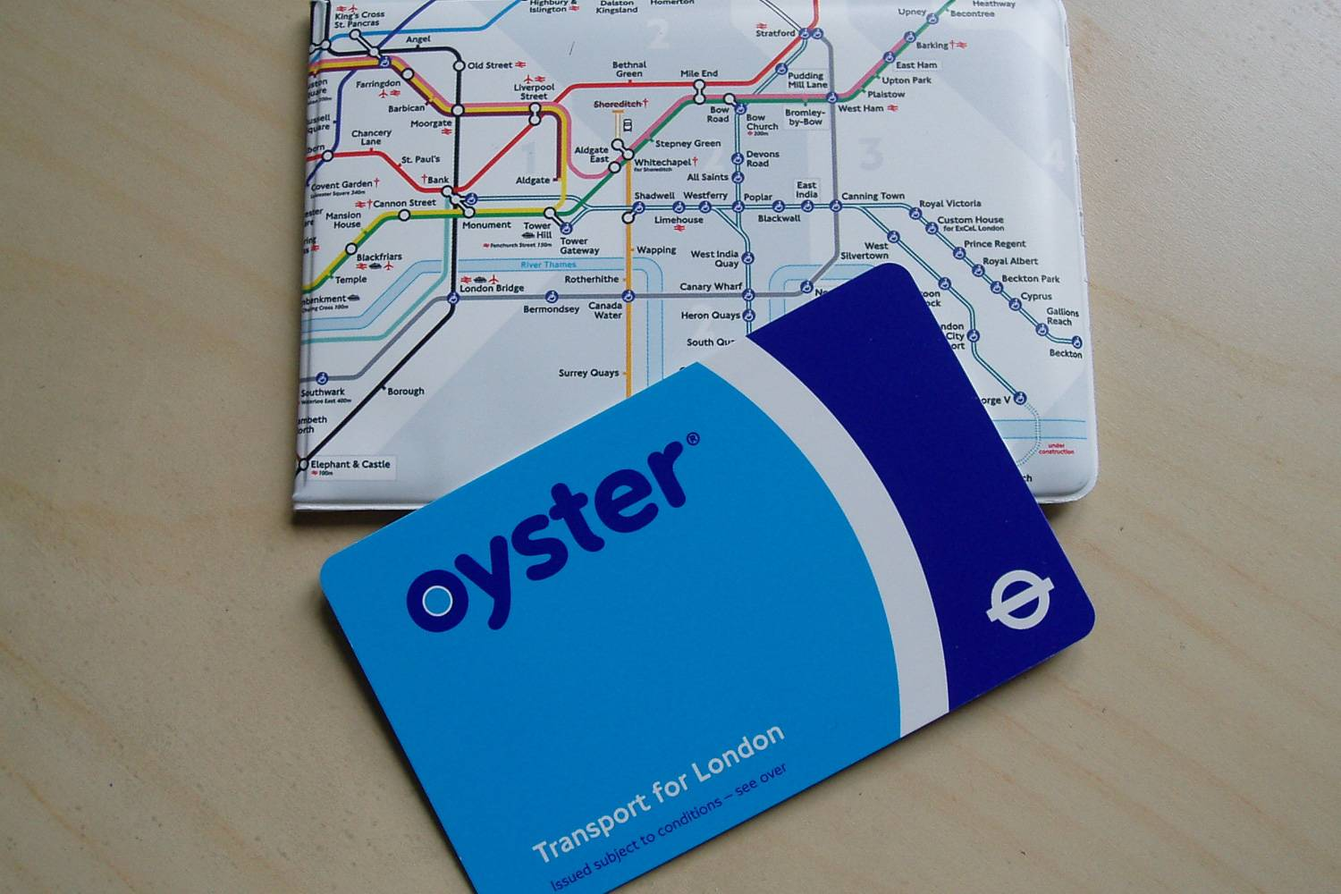 Image of a blue London Oyster card with a carrying case decorated with a map of the Underground.