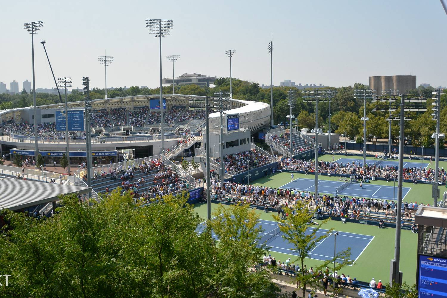 Image of Arthur Ashe Stadium and three tennis courts in Flushing Meadows – Corona Parks.