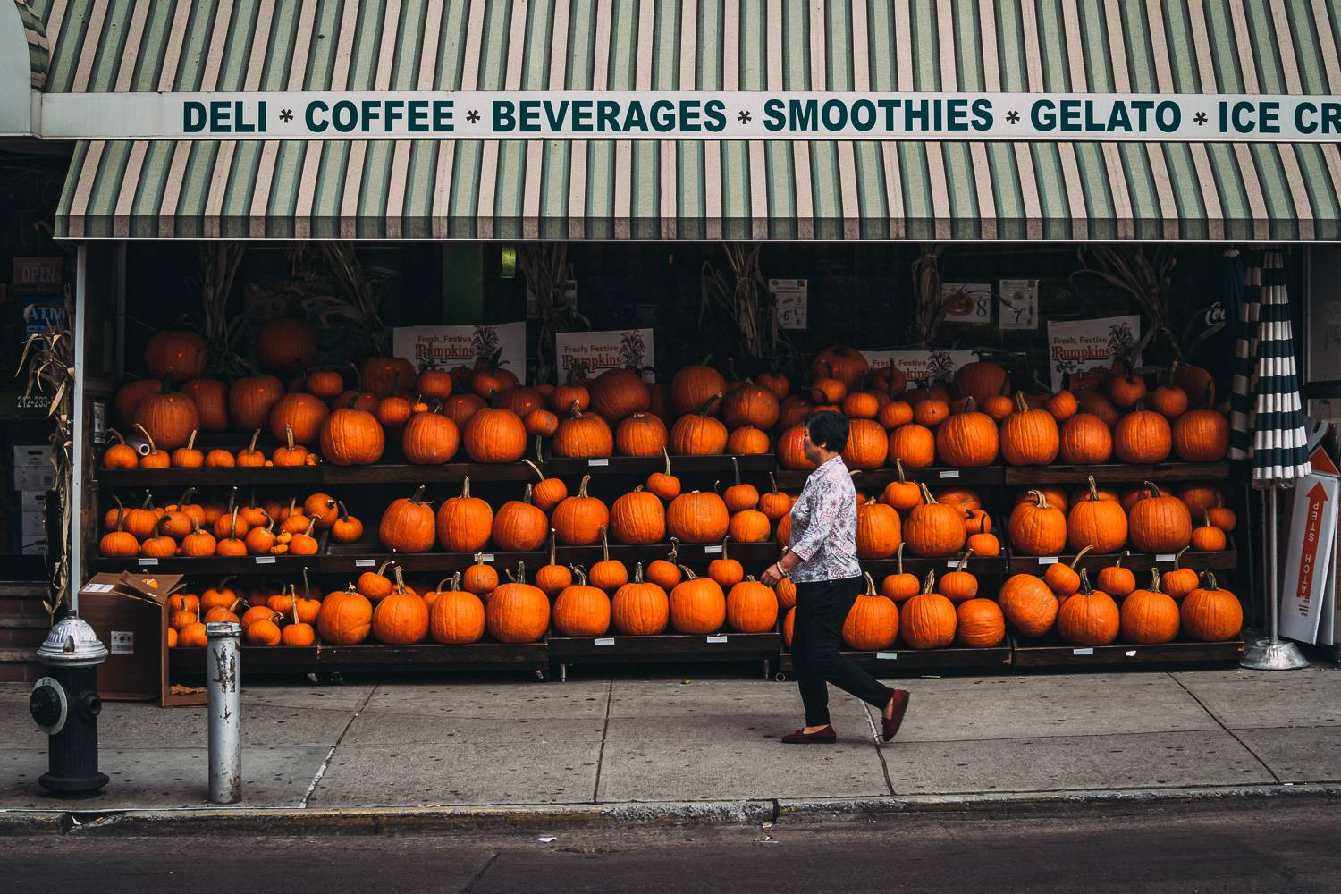 Image of a woman walking by a deli in Chinatown selling pumpkins.