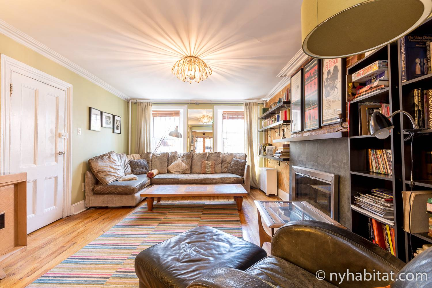 Image of living area of NY-12507 with decorative fireplace, sofa, chandelier, and armchair.