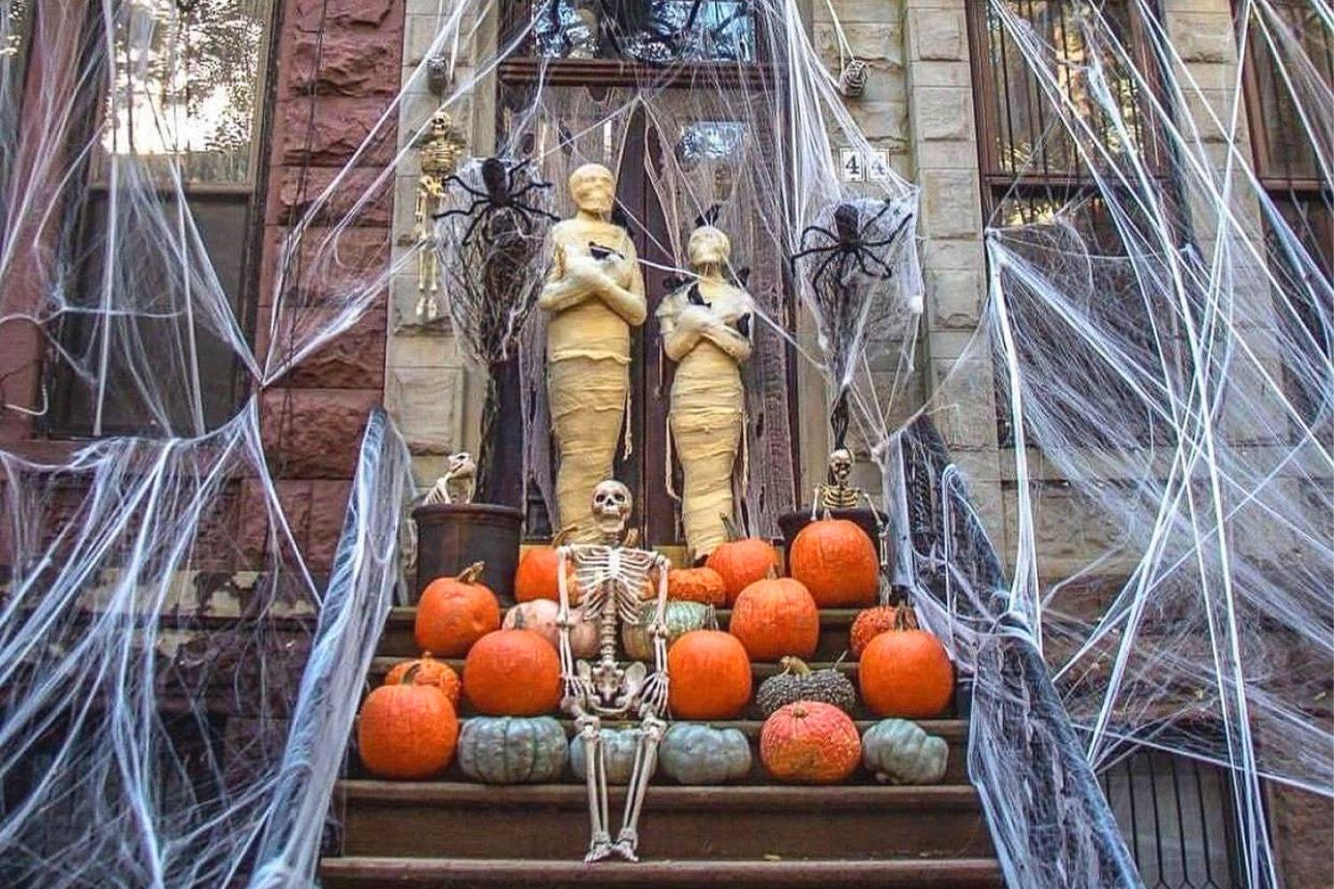 A haunted Manhattan stoop featuring Halloween-themed ghouls, skeletons, gourds, and spider webs.