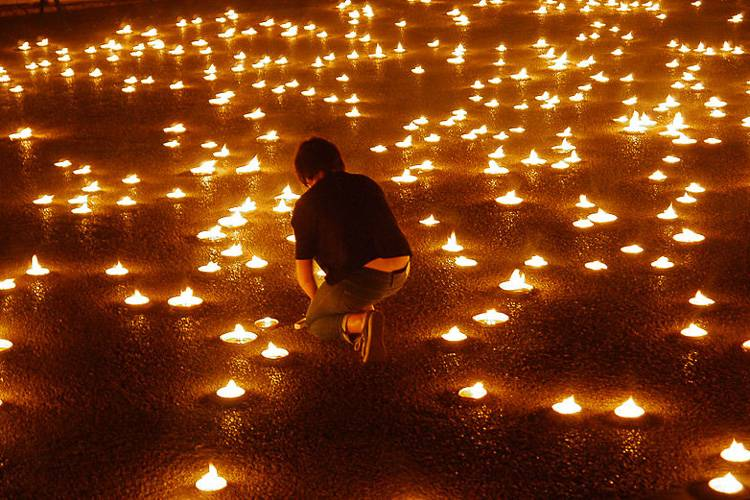 An image of candles burning during a ceremony at the Nuit Blanche arts festival.