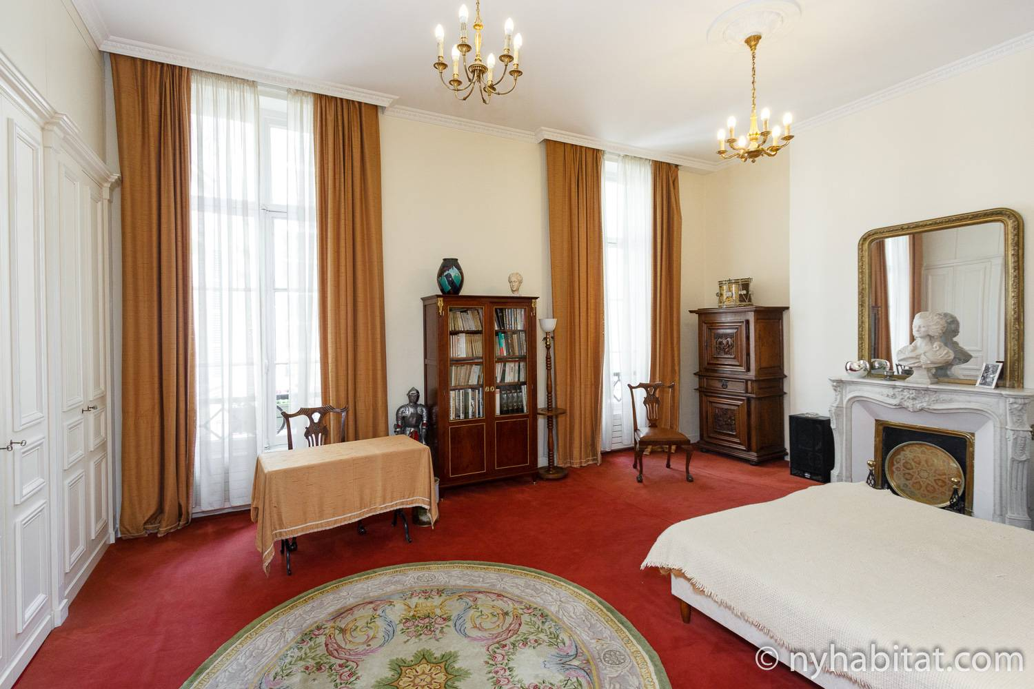 Image of Paris furnished rental PA-3231 with large French windows, chandeliers, decorative fireplace and red carpet.