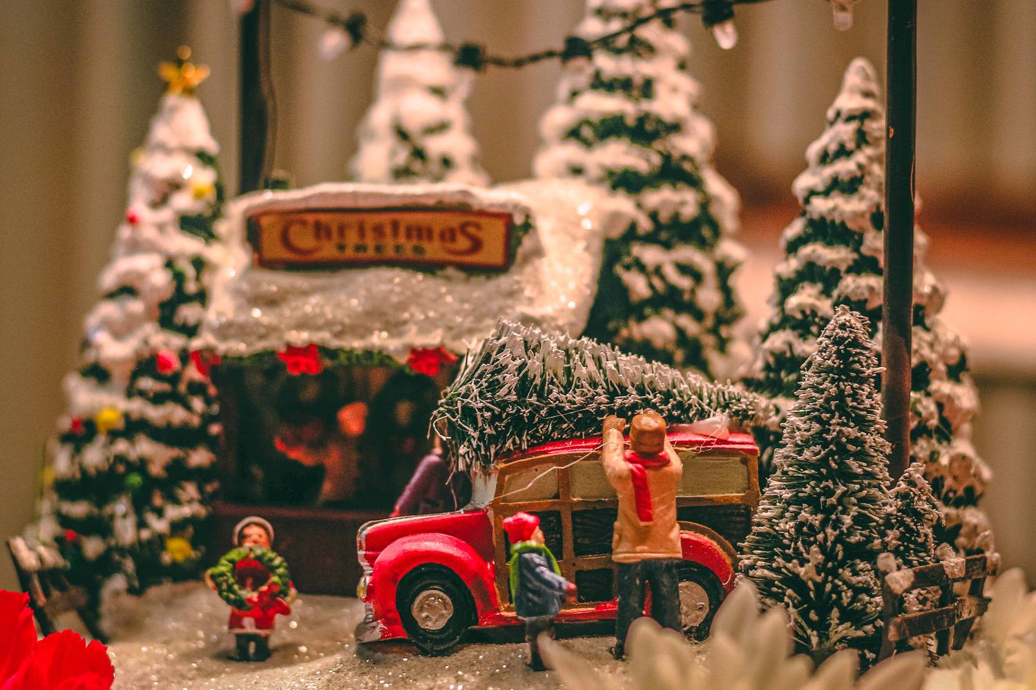 Image of toy replica of family at a Christmas tree stand, tying a tree on top of their car