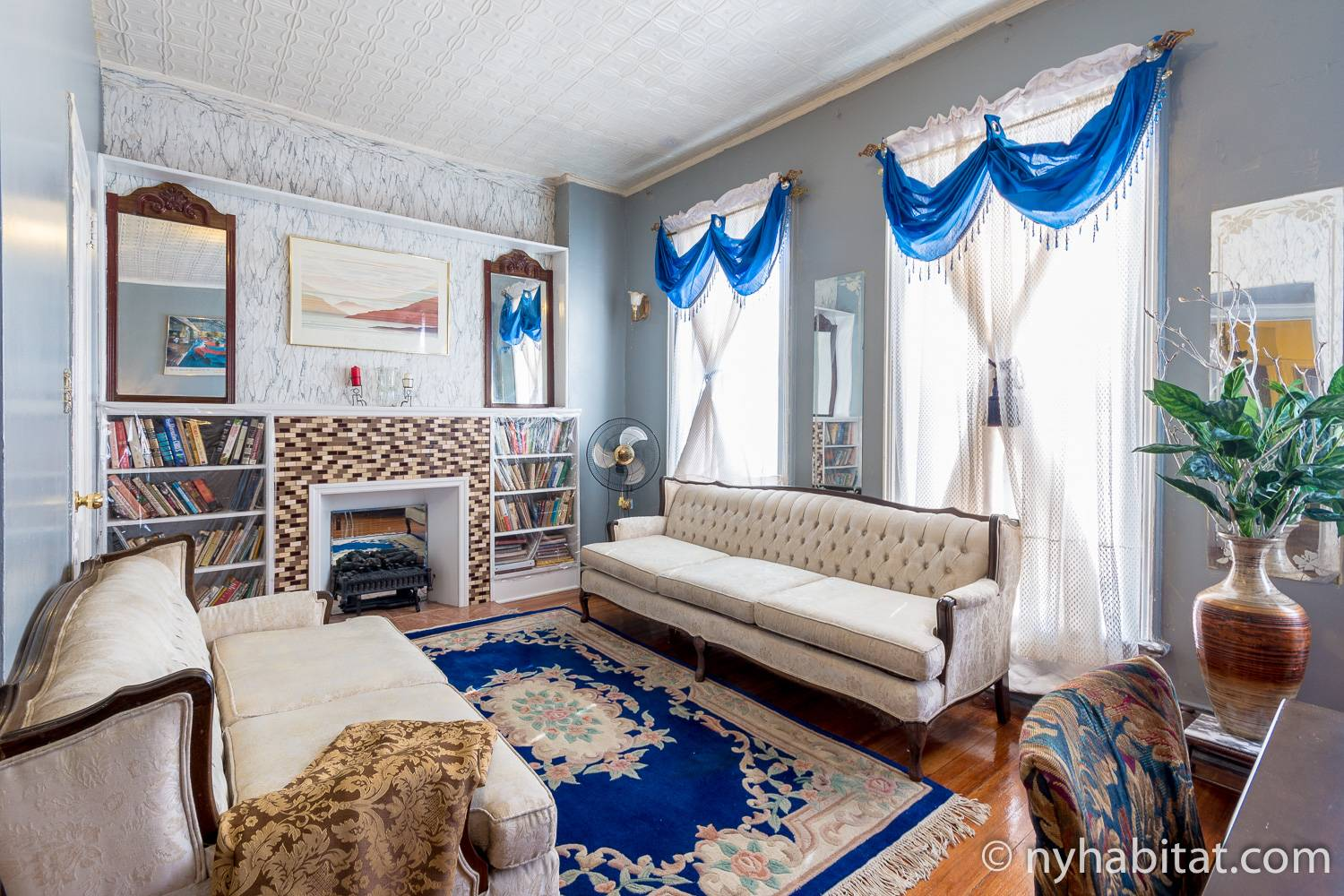 Image of living room of vacation rental NY-15544 with antique sofas around a fireplace