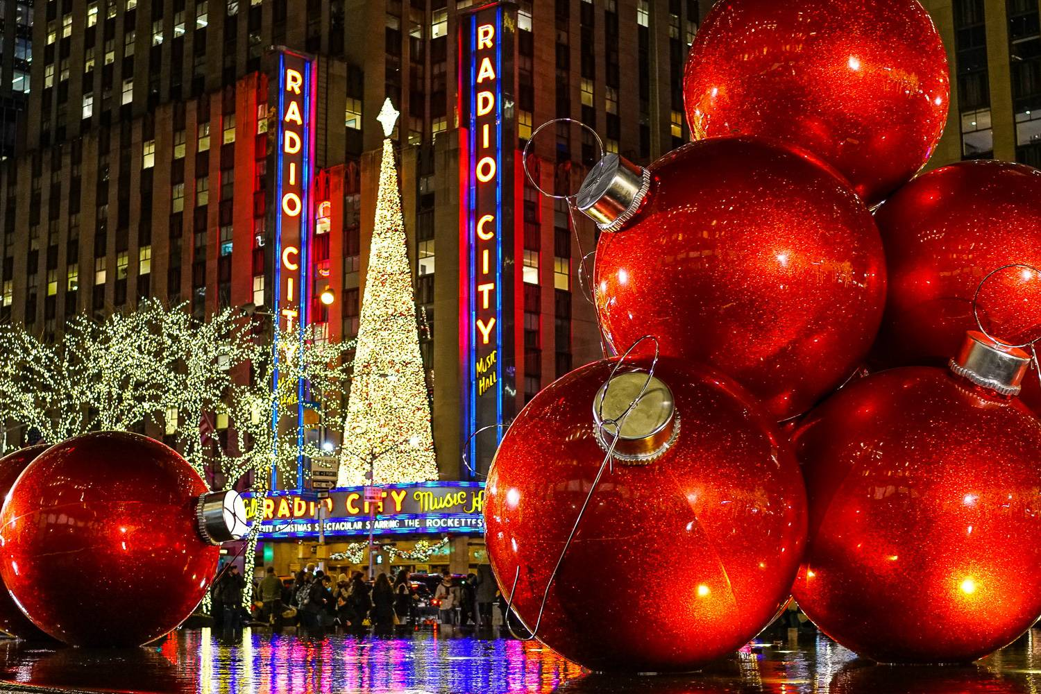 Image of the front of Radio City Music Hall at night with neon lights, Christmas tree over the entrance, trees wrapped in lights and giant red ornaments