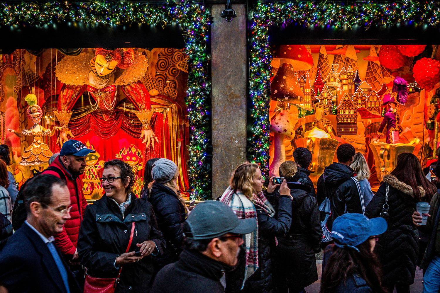 Image of tourists in winter wear outside of store windows decorated for the holidays