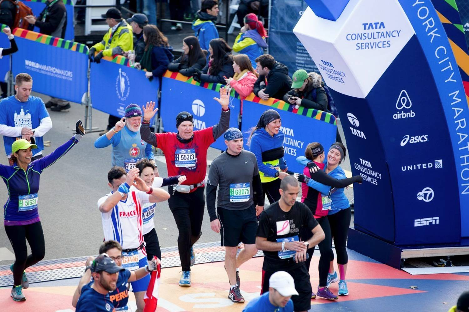 Image of runners cheering and hugging each other as they race past the finish line in the New York City Marathon.