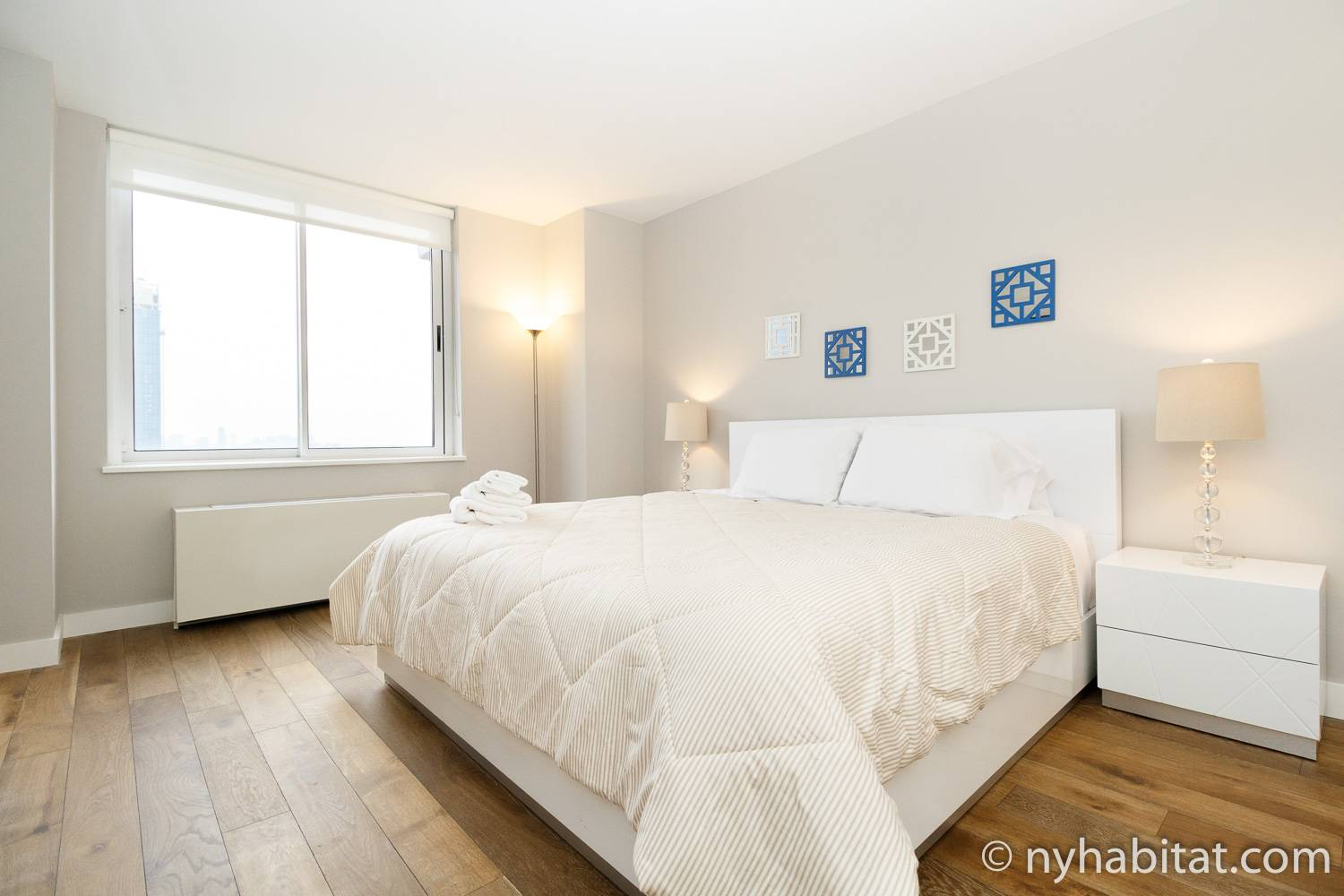 Image of one of the bedrooms in furnished rental NY-17394 with a full sized bed covered in white duvet and blue decorations on the wall.