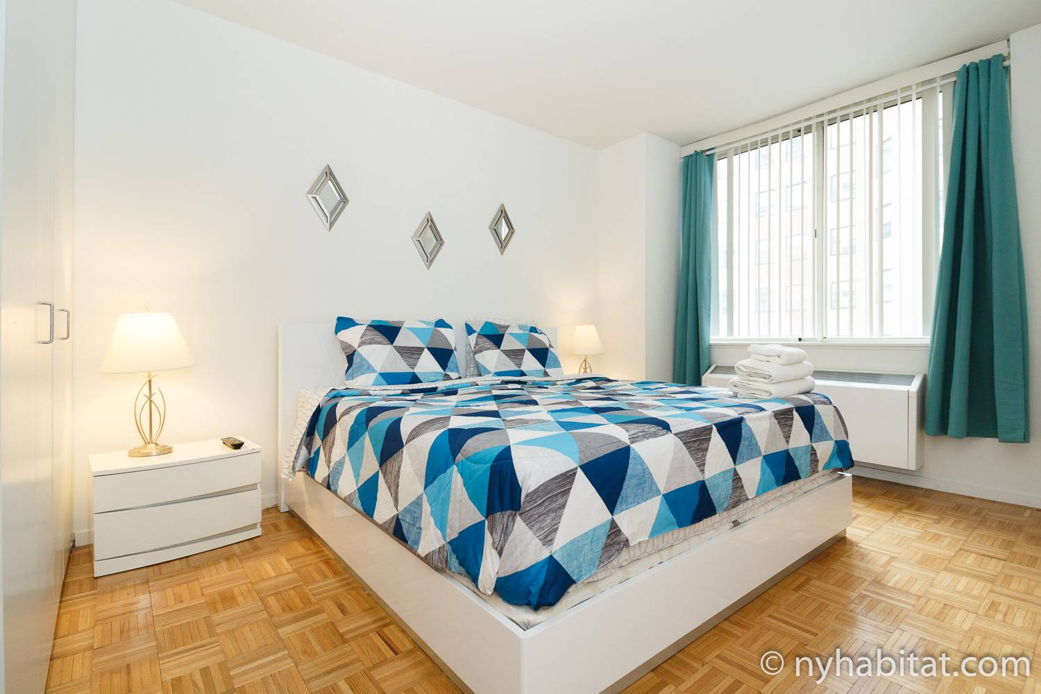 Image of a bedroom in furnished apartment NY-17392 with a king sized bed and two bedside tables with lamps.