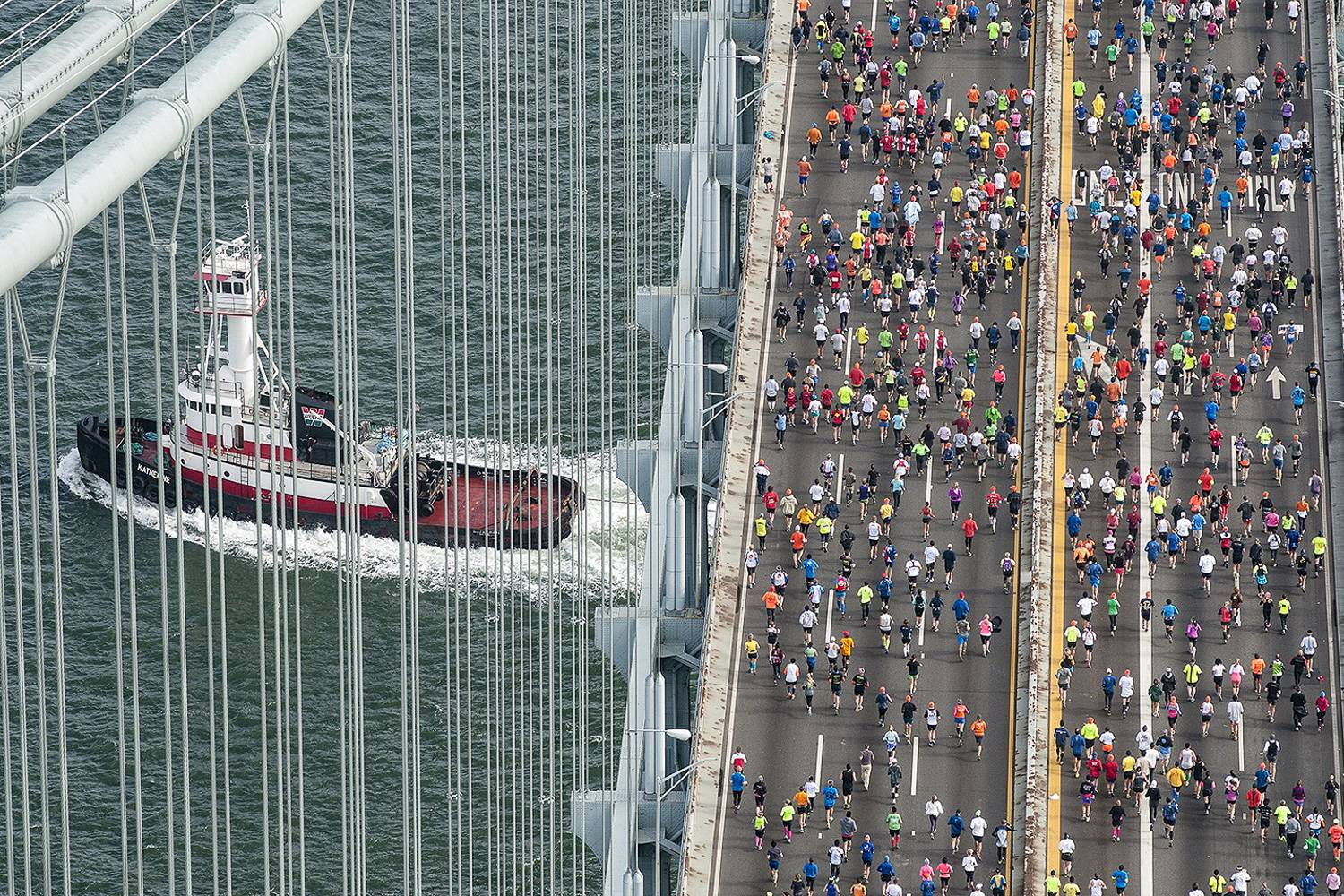 Image of marathoners running across the bridge in the TCS New York City Marathon with a ship passing under the bridge.