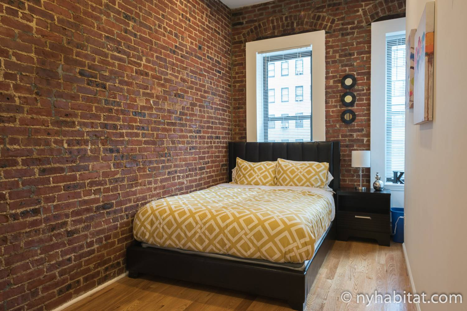Image of bedroom in vacation rental NY-16561 with exposed brick walls and a yellow double bed.