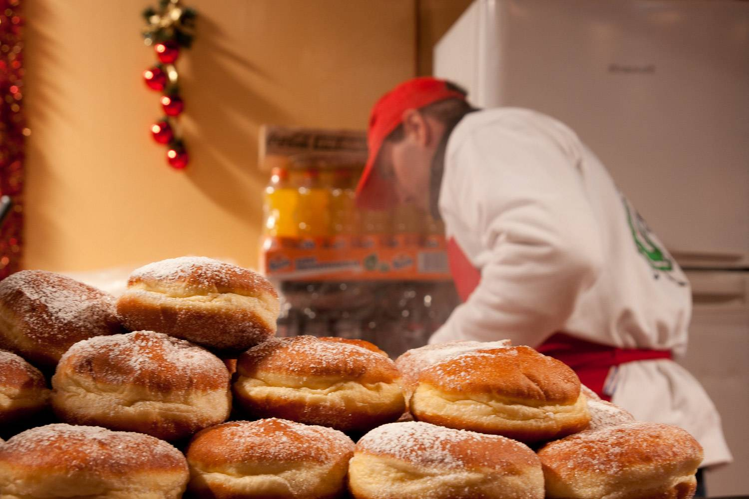 Image of cider donuts in the foreground with the food handler pictured a the back.
