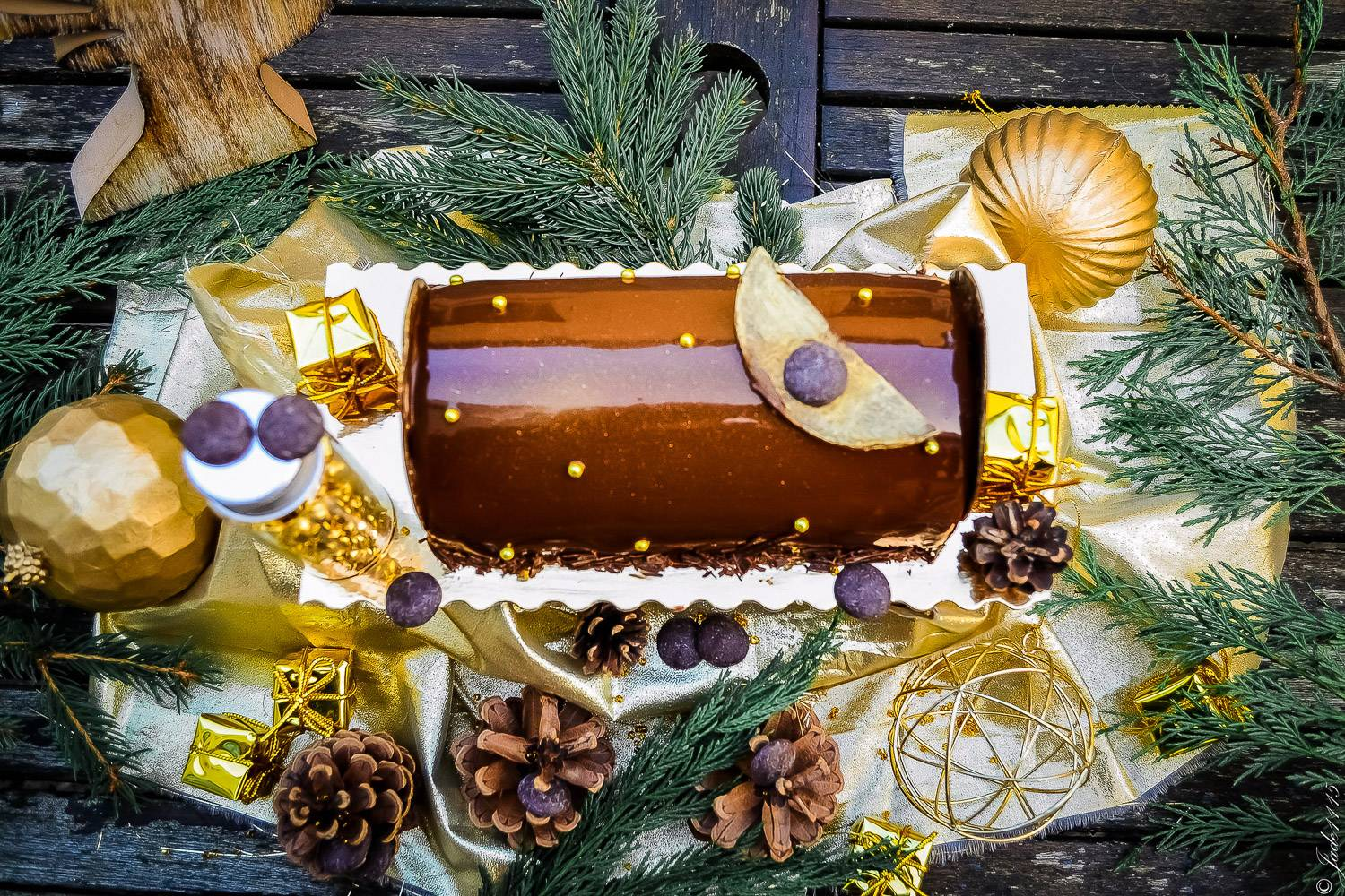 Image of a chocolate Bûche de Noel surrounded by pine cones, leaves and gold Christmas decorations.
