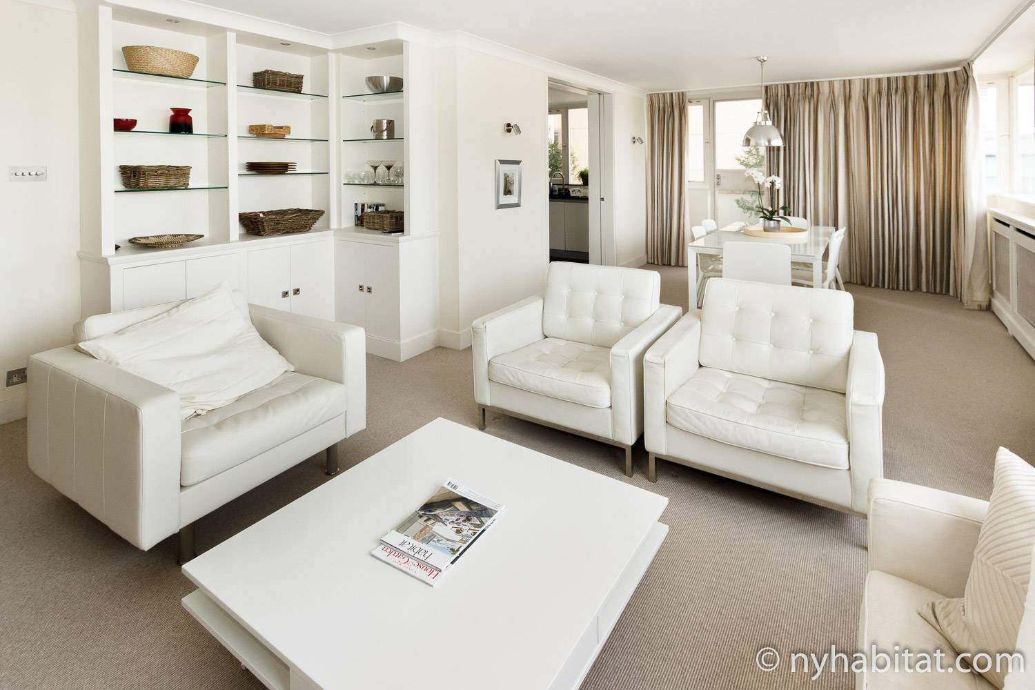 An image of white leather chairs, a coffee table, and modern, clean decorations in London furnished rental LN-1953