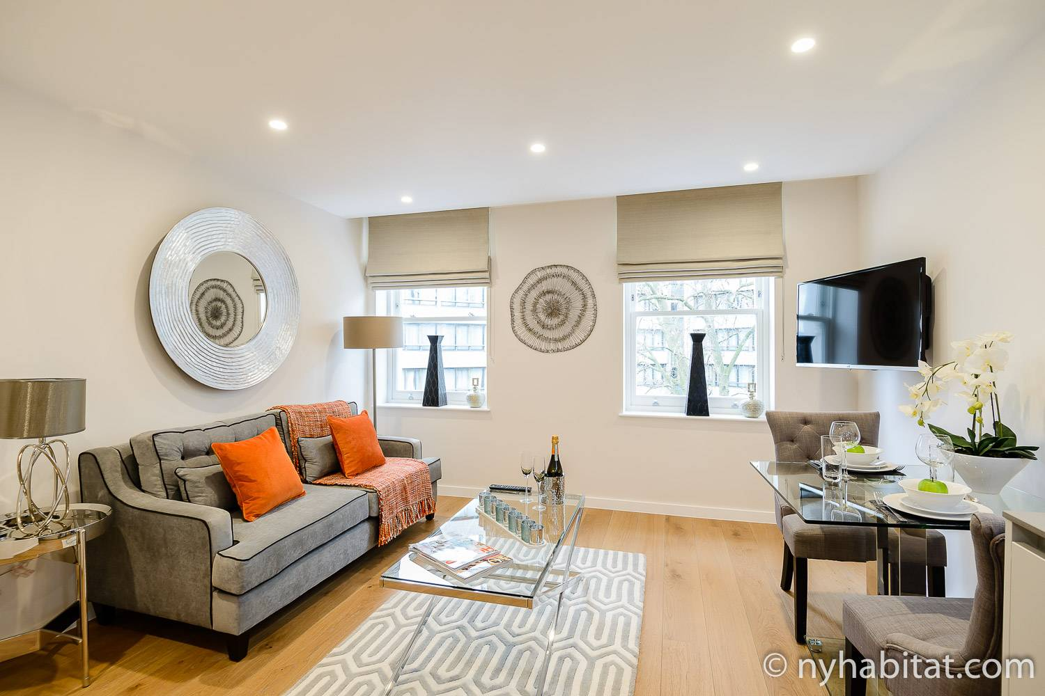 An image of a couch, TV, dining table, with orange accent colors and grey, homey furnishings in London vacation rental LN-1648.