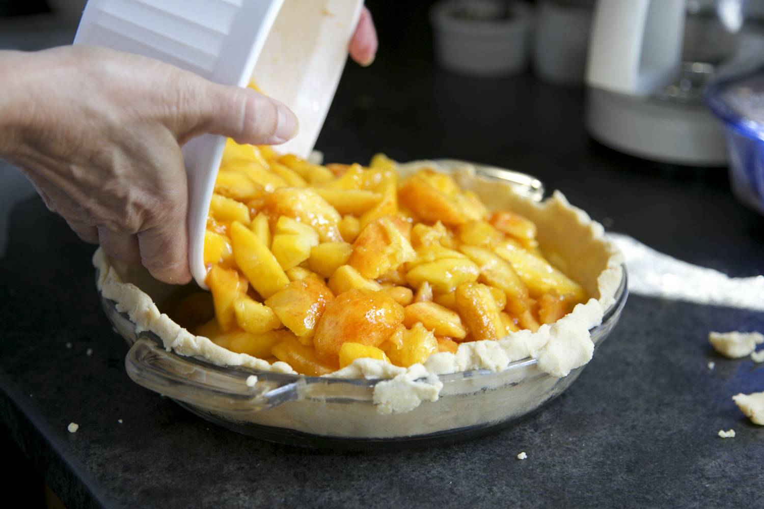 Image of a pie crust being filled with apple in a pie dish.