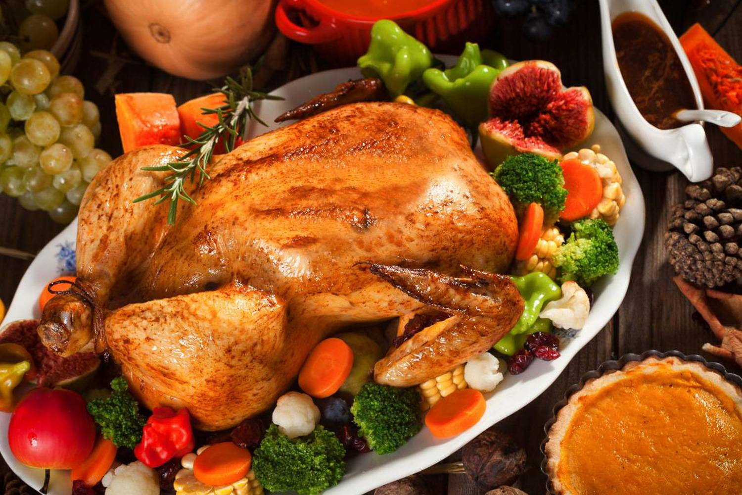 Image of a golden brown turkey in the center of Thanksgiving decorations