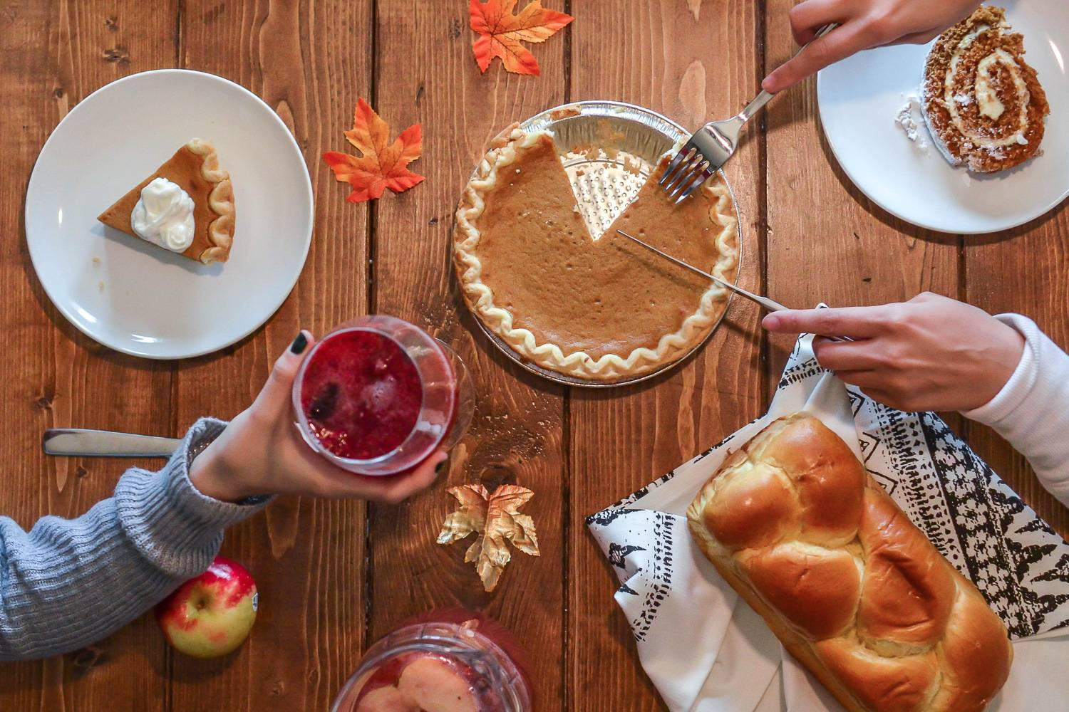 Image of overhead view of a dining table filled with pie, mulled wine, challah bread, and apples.