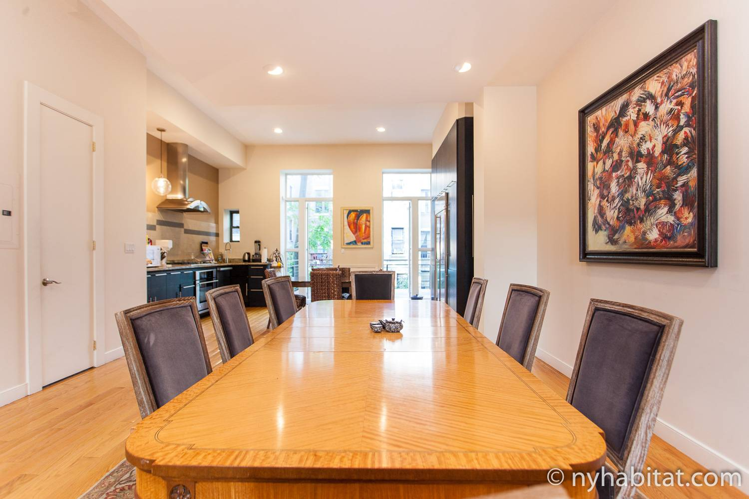 Image of a grand dining table of Harlem vacation rental NY-15383 peering into the open kitchen and balcony entrance.