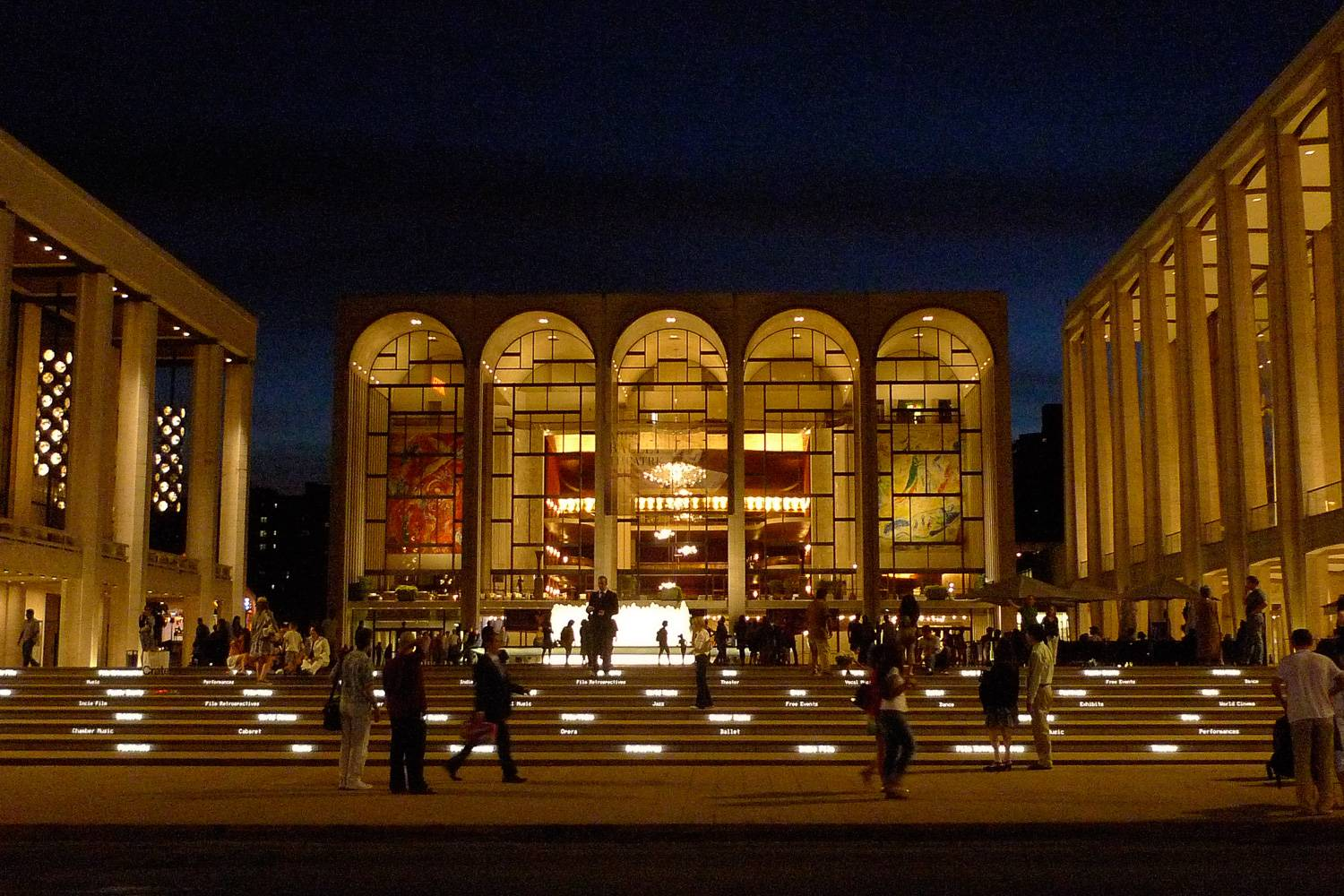Image of Lincoln Center at night with people walking by.