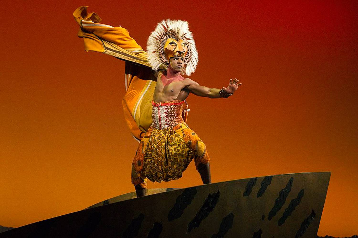 Image of performer dressed in Lion King costume on Broadway