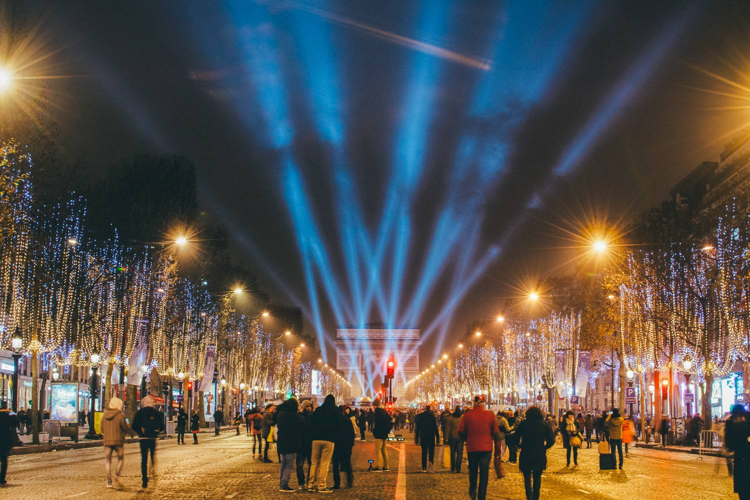 Image of the Champs Élysées light show in Paris and people walking towards it.