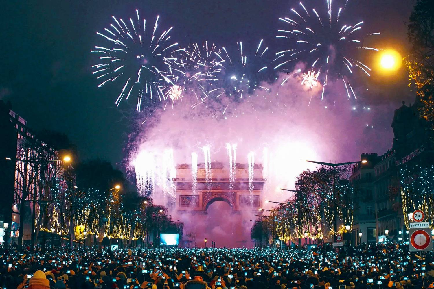Image of thousands gathering in Paris at the front of Champ de Élysées for the midnight light show.