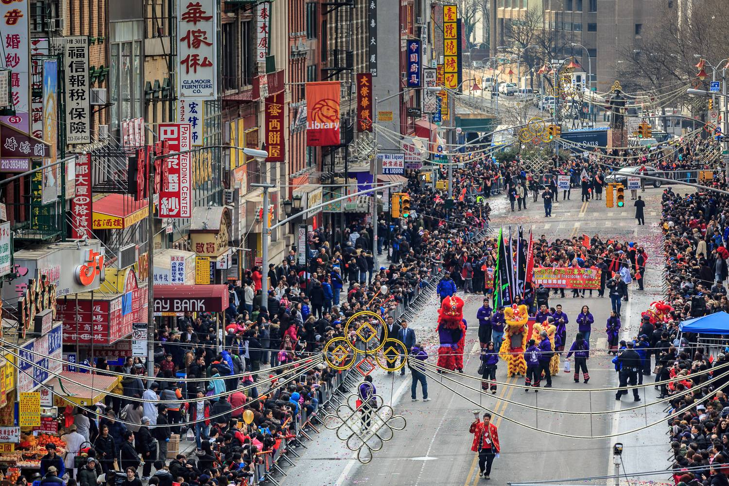 Aerial view of a Chinatown street with a parade for Chinese New Year with signs in Chinese characters
