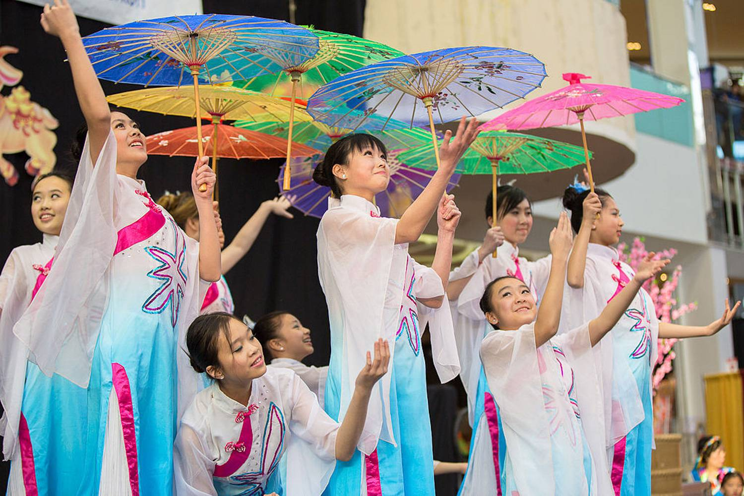 Image of Asian women in traditional dress with parasols dancing