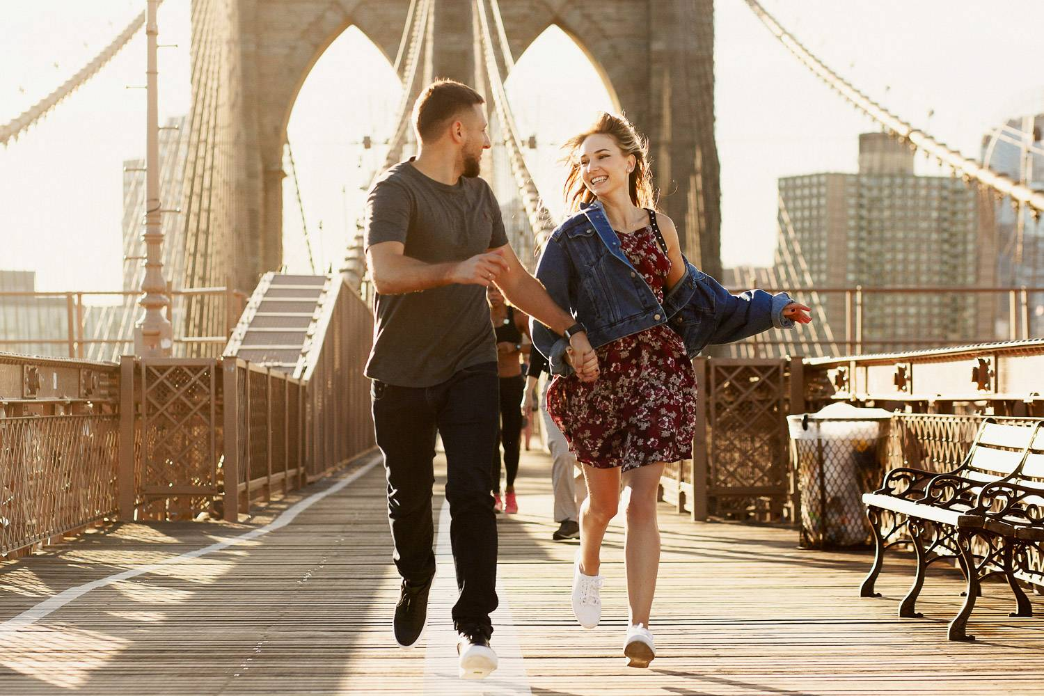 Image of a couple running together on NYC's Brooklyn Bridge