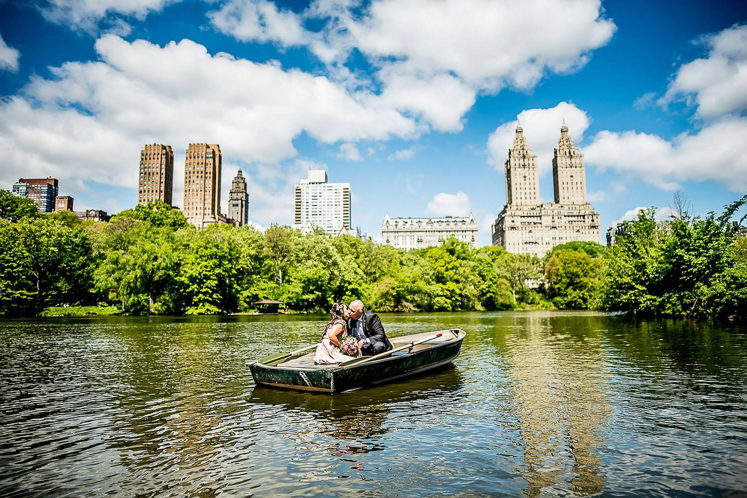 Image of couple kissing with a bouquet of flowers on a row boat in Central Park