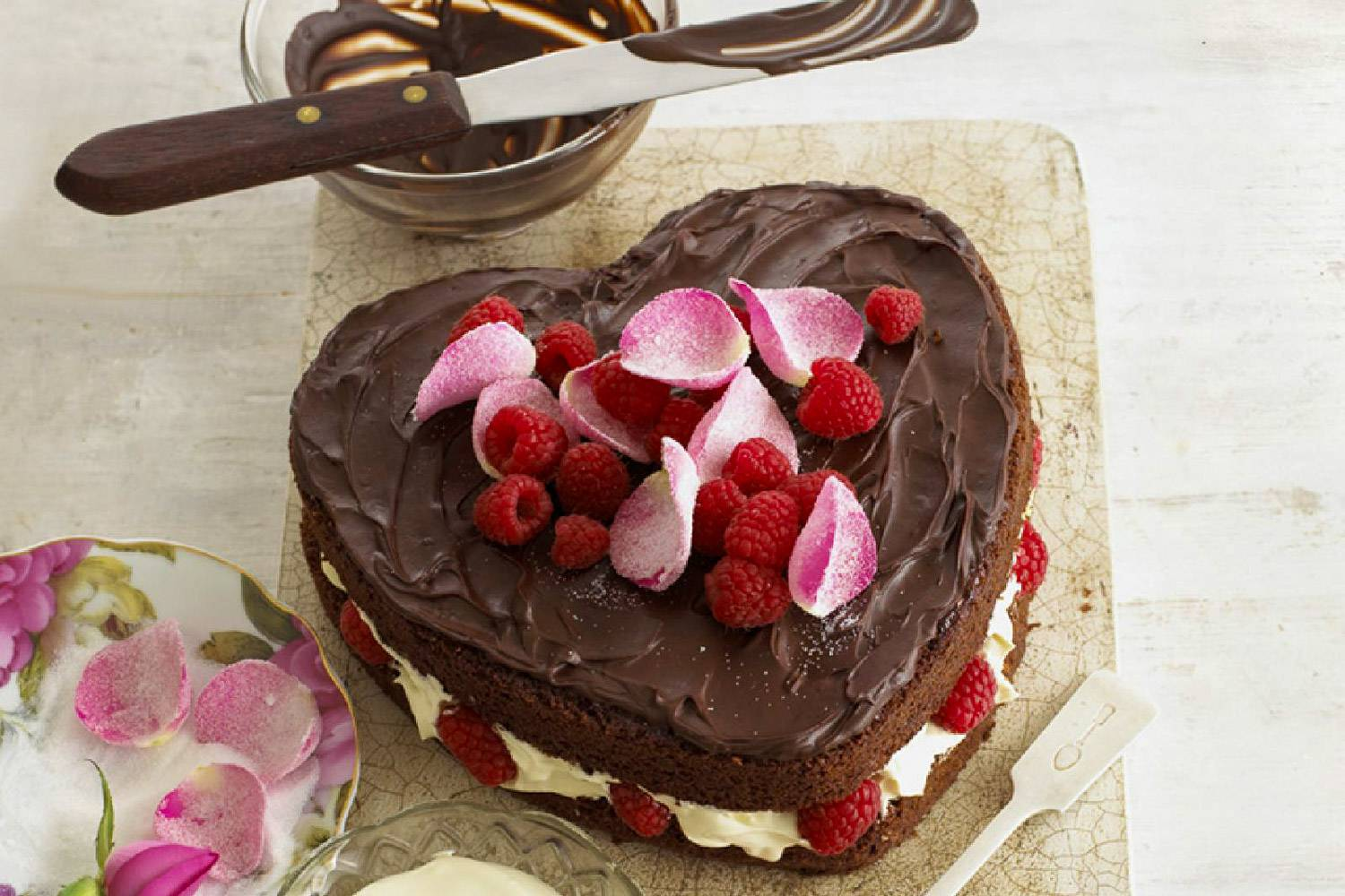 Image of a heart shaped chocolate cake covered with fruit and rose petals and a spatula dipped in chocolate