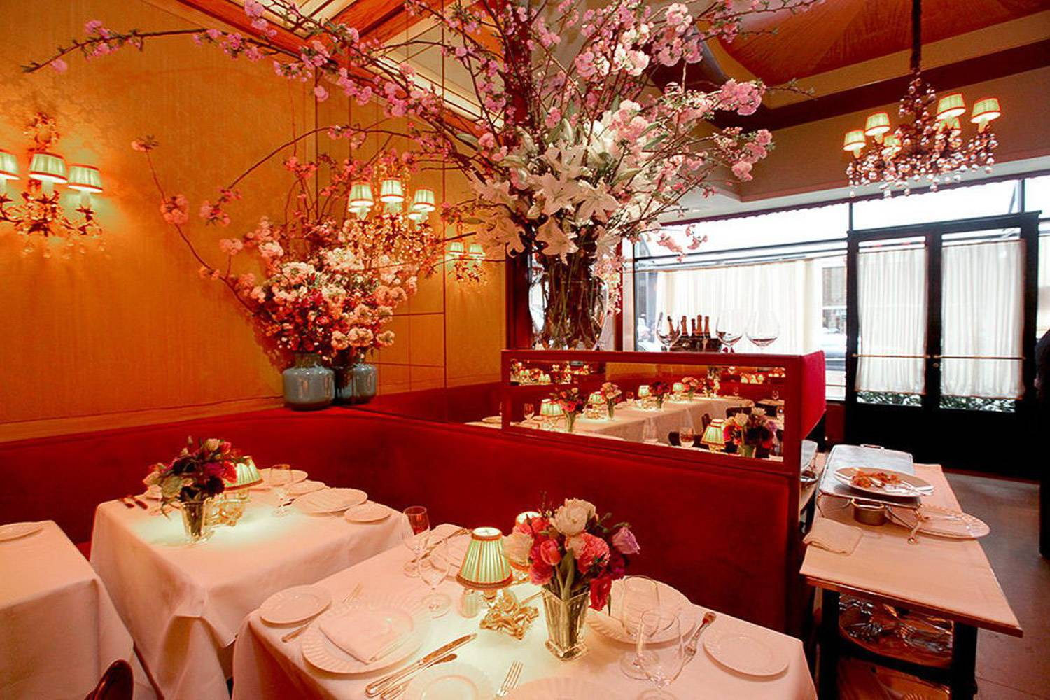 Image of the dining room of La Grenouille French restaurant in NYC decorated all in red with flowers and candles
